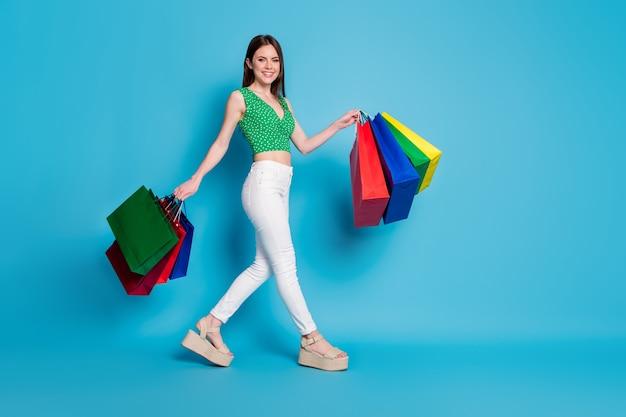 Photo de profil pleine longueur d'une fille joyeuse tenant des sacs aller à pied au centre commercial porter un débardeur vert en pointillé isolé sur un fond de couleur bleu