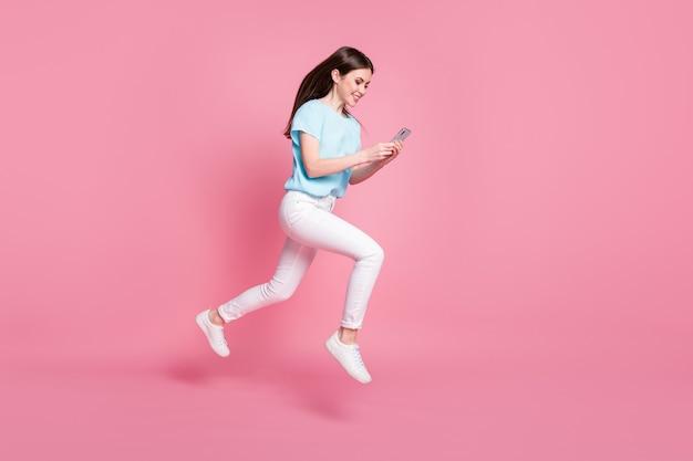 Photo de profil pleine longueur d'une fille sauter utiliser un smartphone courir porter un t-shirt pantalon isolé sur fond de couleur pastel