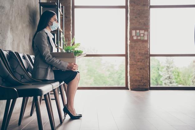 Photo de profil pleine longueur d'une fille sérieuse qui perd son emploi a besoin d'une nouvelle occupation s'asseoir chaise carton boîte attendre pour le recrutement emploi hr entretien porter une veste masque médical dans le poste de travail