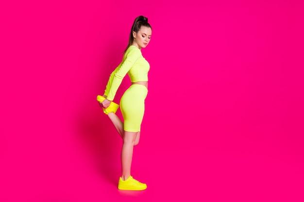 Photo de profil pleine longueur d'une fille sportive étirer les jambes de l'espace vide porter des détectives jaunes isolées sur fond de couleur rose vif