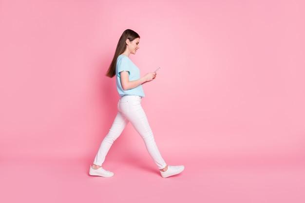 Photo de profil pleine longueur de fille utiliser un téléphone portable pour fond de couleur pastel isolé