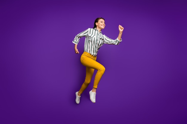 Photo de profil pleine taille de folle belle dame sautant haut se précipiter vers la ligne d'arrivée sportive compétitive porter chemise rayée pantalon jaune isolé fond de couleur pourpre