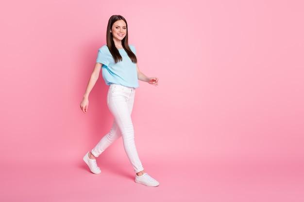 Photo de profil pleine taille de nice girl go copyspace isolé sur fond de couleur rose
