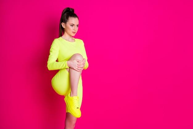La photo de profil de la sportive active les jambes étirées a l'air d'un espace vide isolé sur fond de couleur rose vif