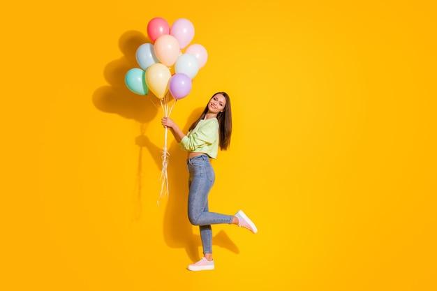 Photo de profil en taille réelle d'une jolie dame tenant de nombreux ballons à air