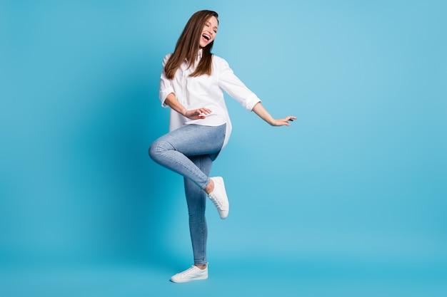 Photo de profil sur toute la longueur d'une fête de danse folle portant une chemise blanche jeans baskets isolé sur fond de couleur bleu