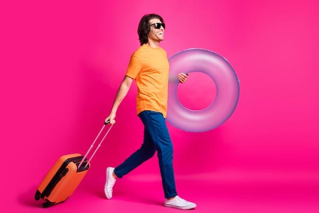 Photo de profil sur toute la longueur d'un gars qui va tenir le cercle en caoutchouc de l'affaire porter un t-shirt orange jeans chaussures de lunettes de soleil isolé sur fond de couleur rose
