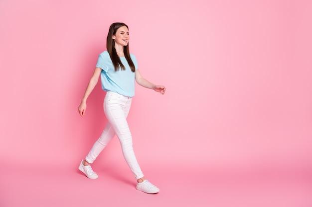 Photo de profil sur toute la longueur de la jolie fille qui va dans l'espace vide porter des baskets isolées sur fond de couleur rose