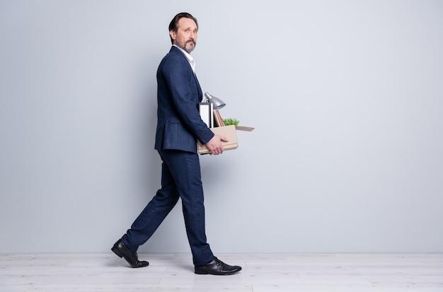 Photo de profil sur toute la longueur d'un travailleur mécontent d'un homme âgé crise financière crash perdu emploi transporter boîte de transport personnel licencié à pied quittant le bureau déçu porter un costume bleu isolé sur fond gris