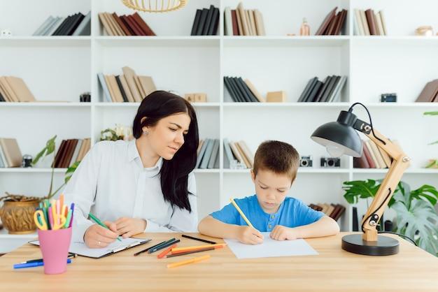 Photo de psychologue pour enfants travaillant avec un jeune garçon au bureau