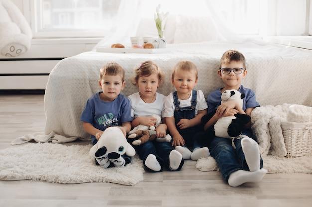 Photo de quatre petits enfants en vêtements de maison assis près du canapé blanc avec des jouets, sourire et s'amuser