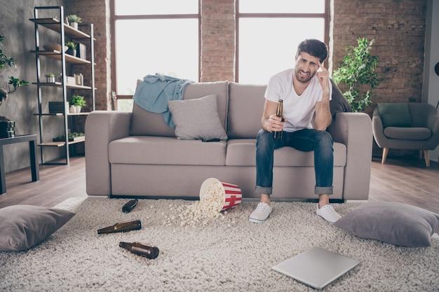 Photo de race mixte guy assis canapé tenant une bouteille de bière pop-corn sur le sol avait un divertissement fou après la fête souffrent de la gueule de bois matin mal de tête malpropre à l'intérieur