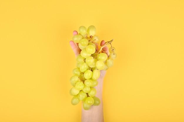 Photo de raisin vert sur fond jaune. raisins volumétriques. une grappe de raisin vert.