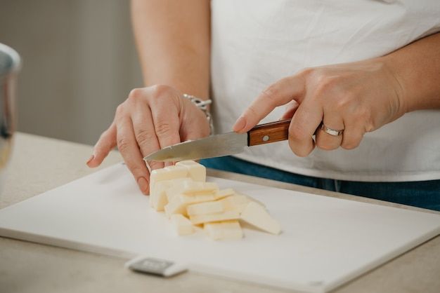 Ð photo rapprochée des mains d'une jeune femme qui coupe du beurre de ferme frais sur une planche à découper avec un couteau bien aiguisé.