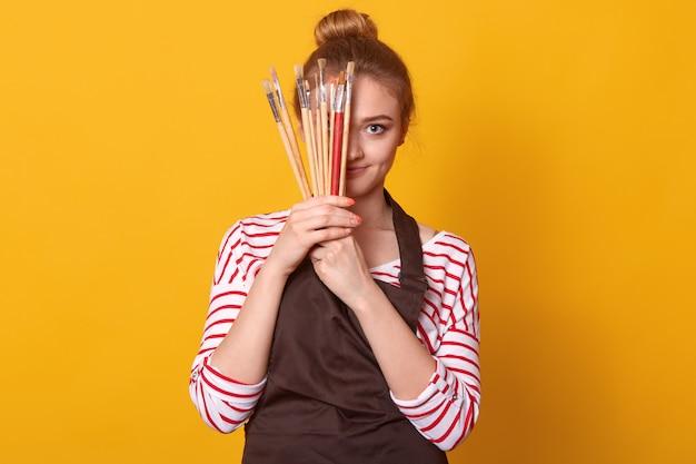 Photo de ravissante tendre jolie jeune femme tenant beaucoup de pinceaux dans les deux mains, couvrant la moitié du visage avec du matériel d'art
