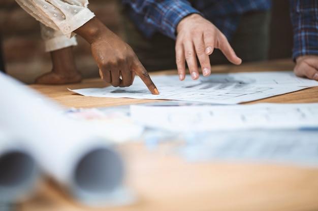 Photo recadrée d'architecte et ingénieur professionnel discutant ensemble du plan de construction