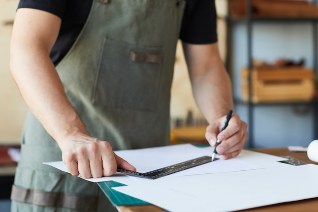 Photo recadrée d'un artisan portant un tablier tout en créant des motifs dans l'espace de copie de l'atelier des tanneurs