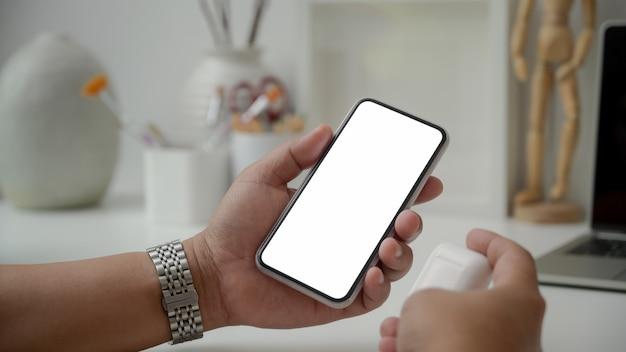 Photo recadrée d'un artiste masculin tenant un casque sans fil et un smartphone à écran vide