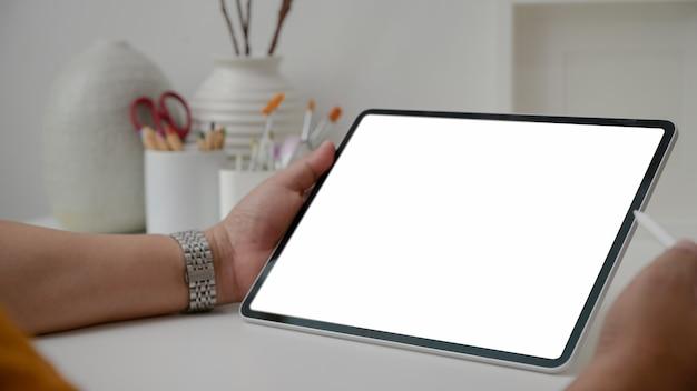 Photo recadrée d'un artiste masculin travaillant sur une tablette à écran blanc avec un stylet, des outils de peinture et une décoration