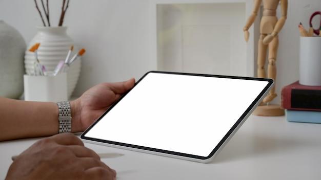 Photo recadrée d'un artiste masculin travaillant sur une tablette à écran vide avec un stylet, des outils de peinture et des décorations