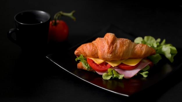 Photo recadrée d'une assiette de petit-déjeuner avec un croissant sandwich au jambon et fromage frais