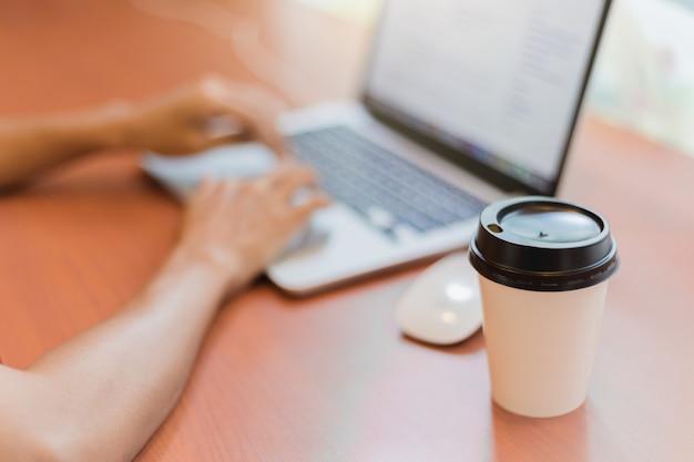 Photo recadrée au café travaillant sur son ordinateur portable. à l'aide d'un ordinateur portable avec une tasse de café sur la table.