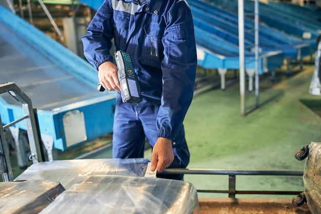 Photo recadrée d'un bagagiste scannant un code-barres sur une étiquette de bagage tout en triant les sacs des passagers