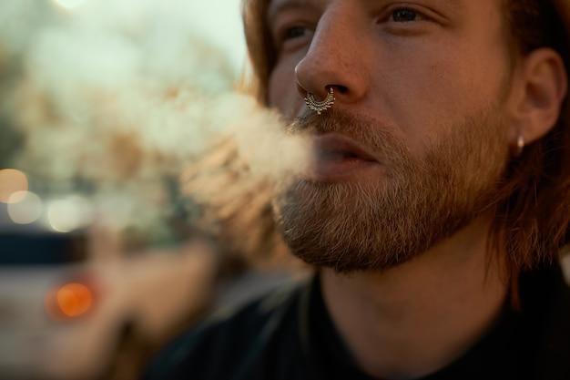 Photo recadrée de beau jeune homme barbu cigarette électronique vaping à l'extérieur. près d'un mec attrayant avec anneau de nez soufflant de la fumée en marchant sur la rue de la ville aux beaux jours d'été