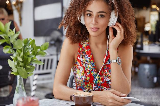Photo recadrée d'un beau modèle féminin afro-américain confiant, écoute la piste audio dans les écouteurs
