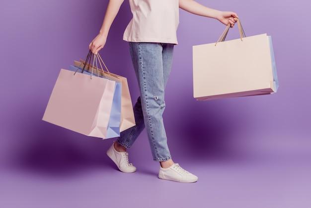 Photo recadrée d'une belle femme marchant avec des bonnes affaires du temps de magasinage sur un mur violet