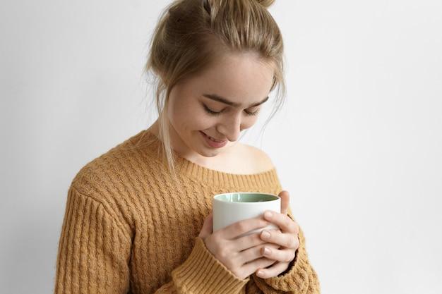 Photo recadrée de la belle jeune femme européenne habillée avec désinvolture avec chignon posant dans un pull surdimensionné tenant une tasse à deux mains, regardant vers le bas et souriant timidement. repos et relaxation