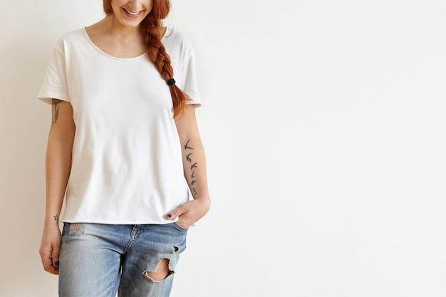 Photo recadrée de la belle jeune femme rousse élégante avec tresse et tatouages souriant joyeusement