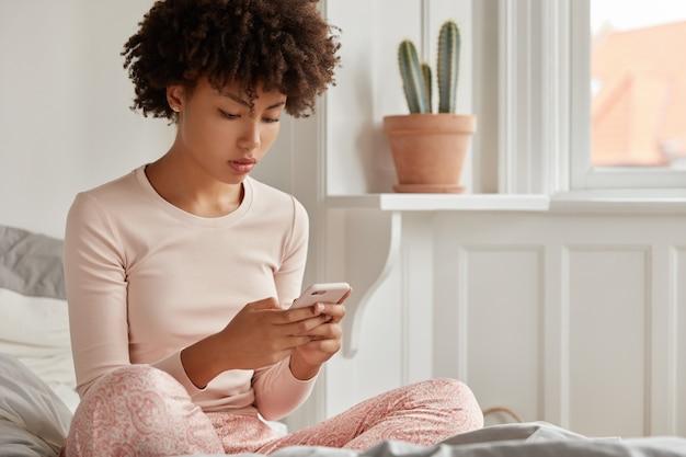 Photo recadrée d'une blogueuse jeune femme avec coupe de cheveux afro, habillée en pyjama, tient un téléphone intelligent