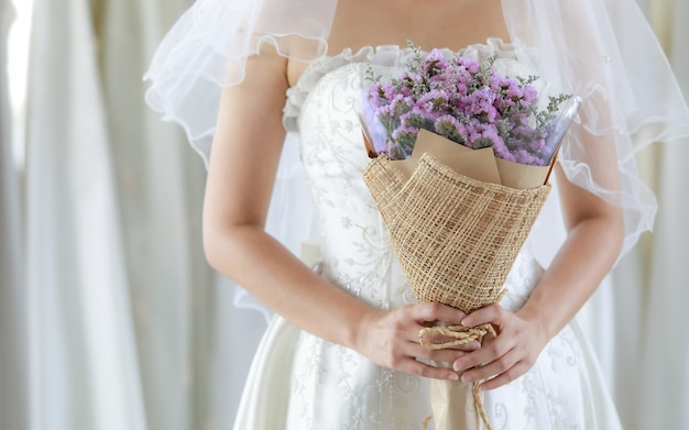 Photo recadrée d'un bouquet de fleurs de mariage violet tenu dans les mains d'une mariée méconnaissable en robe blanche avec un voile de cheveux transparent debout, regardant la caméra en arrière-plan flou dans le dressing.