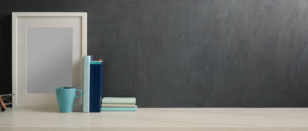 Photo recadrée de bureau à domicile avec maquette de cadre, livres, tasse et espace de copie
