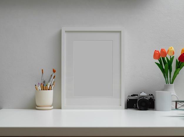 Photo recadrée de bureau à domicile avec maquette de cadre, pinceaux, appareil photo, vase à fleurs et espace de copie