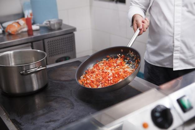 Photo recadrée d'un chef professionnel faisant frire des légumes hachés sur la poêle dans la cuisine du restaurant