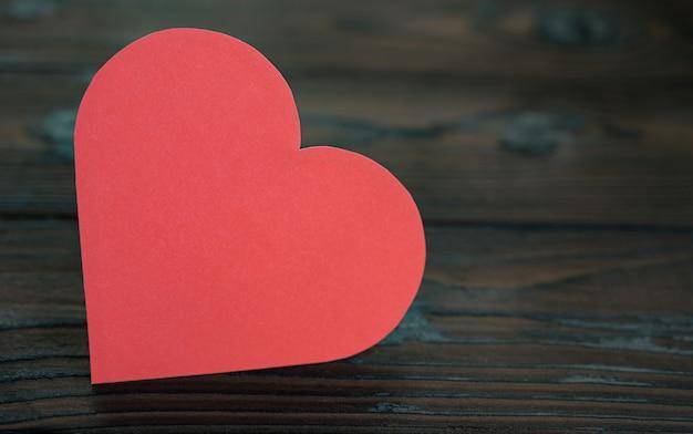 Photo recadrée de coeur de papier rouge sur fond de bois de feu pour la saint-valentin.