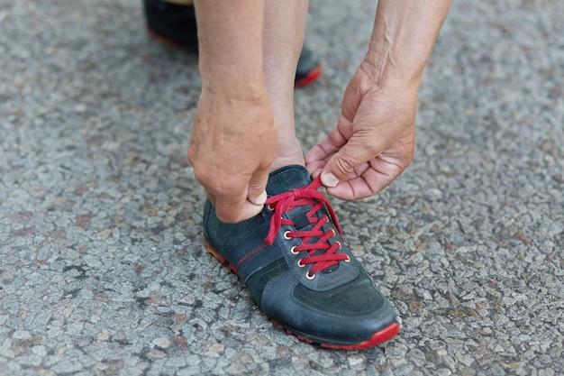 Photo recadrée de collants de mains d'homme mûr chaussures de course lacets, se dresse sur l'asphalte avant la course du matin, en plein air en zone rurale. le coureur masculin attache des chaussures de sport, a une séance d'entraînement pendant la journée d'été
