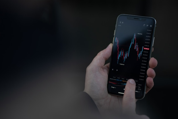 Photo recadrée d'un commerçant gérant des investissements et des actions commerciales dans une application mobile, une main masculine touchant l'écran d'un smartphone avec un graphique financier. marché boursier et concept de négociation en ligne