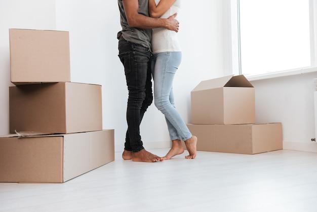 Photo recadrée d'un couple heureux s'embrassant tout en se tenant près de boîtes non emballées.