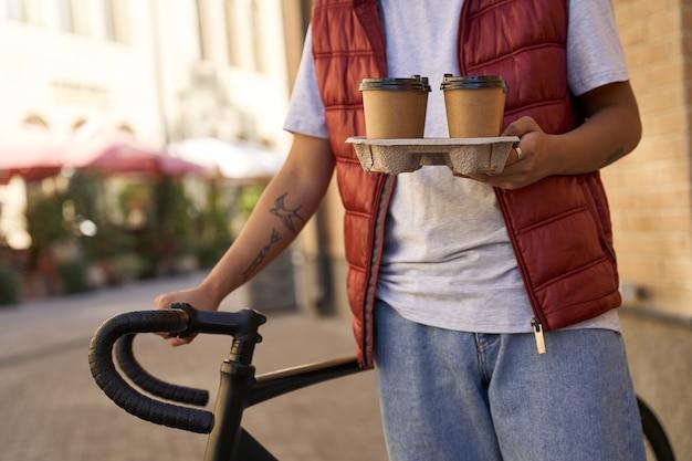 Photo recadrée d'un coursier mâle livrant quatre tasses de café à cu