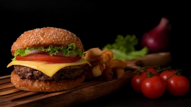 Photo recadrée d'un délicieux hamburger de boeuf fait maison avec des ingrédients et des frites