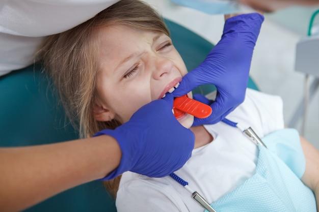 Photo recadrée d'un dentiste faisant des empreintes de dents d'une mâchoire d'enfant avec du mastic dentaire