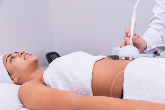 Photo recadrée d'un dermatologue professionnel effectuant une procédure de levage par radiofréquence sur le ventre d'une femme. cliente recevant un traitement de levage rf sur son ventre à la clinique de cosmétologie