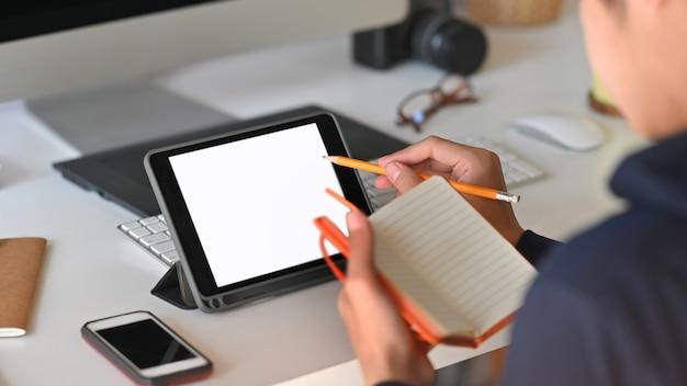 Photo recadrée derrière l'homme intelligent prendre des notes tout en utilisant une tablette informatique à écran blanc et assis à la table de travail moderne avec un lieu de travail confortable
