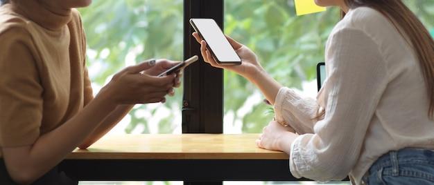 Photo recadrée de deux adolescentes utilisant un smartphone et se parlant