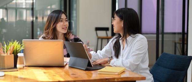 Photo recadrée de deux étudiantes ayant une conversation tout en faisant un travail de groupe