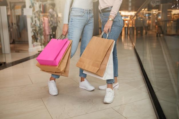 Photo recadrée de deux femmes en vêtements décontractés tenant des sacs en papier au centre commercial
