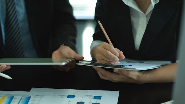 Photo recadrée de deux hommes d'affaires consultant sur leur travail avec graphique et tablette